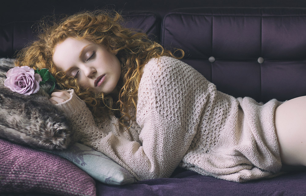 Image of redhaired model Ivory Flame sleeping with purple rose by photographer Rob Ellis